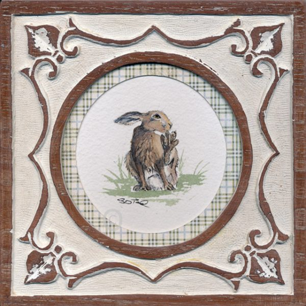 small watercolour illustration of a grooming hare set in a carved hard wood frame with white paint in the carved surface