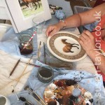 artist Susan Taylor painting in oils on a Harrods Villeroy and Boch plate