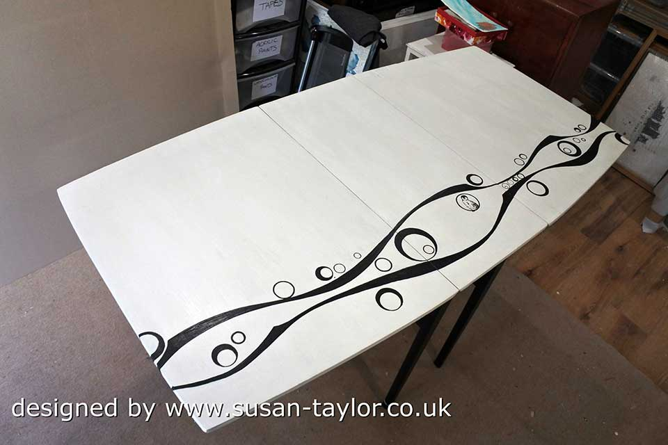old 1960's leaf table has been painted white white with black curvy line and concentric circle design and black legs. giving it a contemporary feel